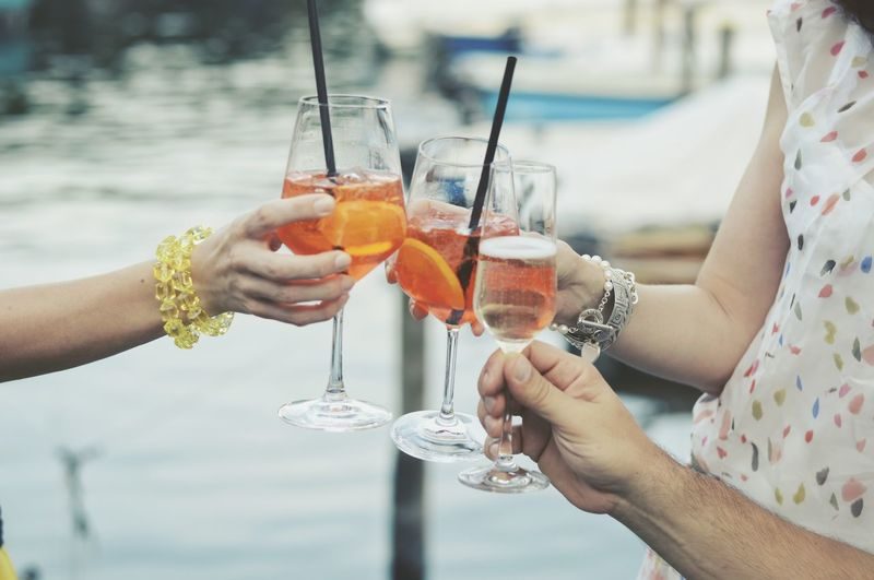 Cropped Image Of Hands Toasting Up Drinks