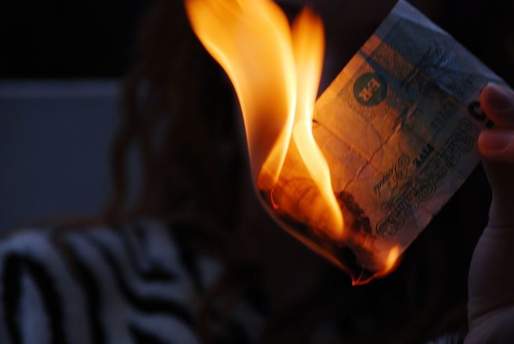 Cropped Image Of Woman Burning Paper Currency