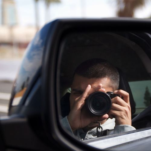 Man photographing by camera in car