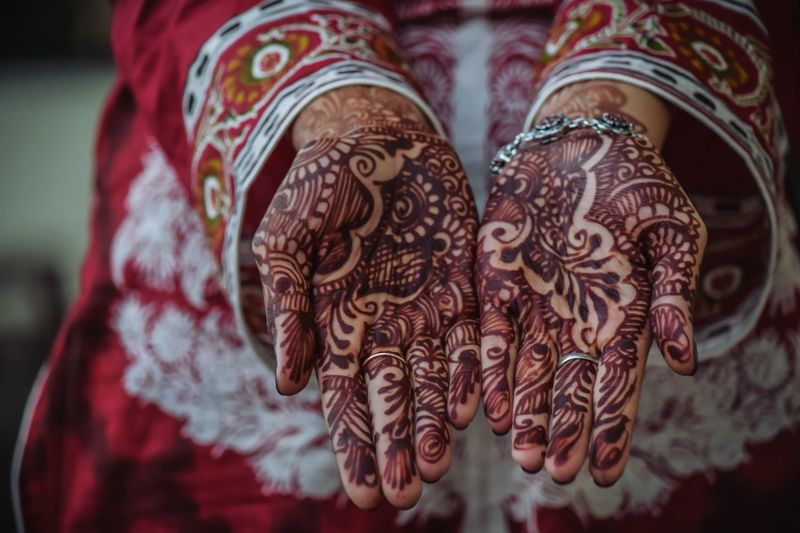 Midsection of bride showing henna tattoo on hands