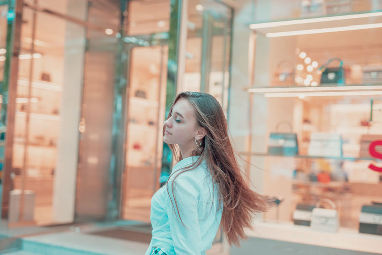 Young woman with eyes closed standing in store window