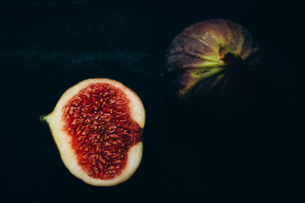 Close-Up Of Halved Fig Against Black Background