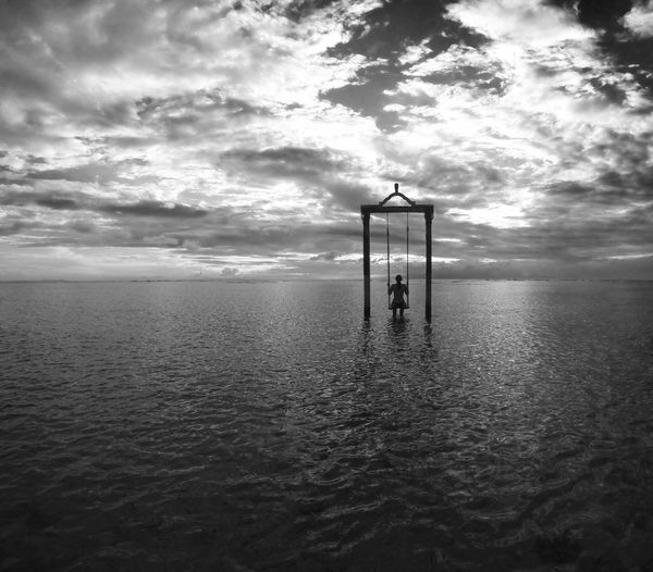 Person swinging in sea against cloudy sky