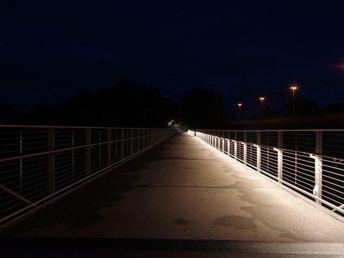 Narrow footbridge along trees at night