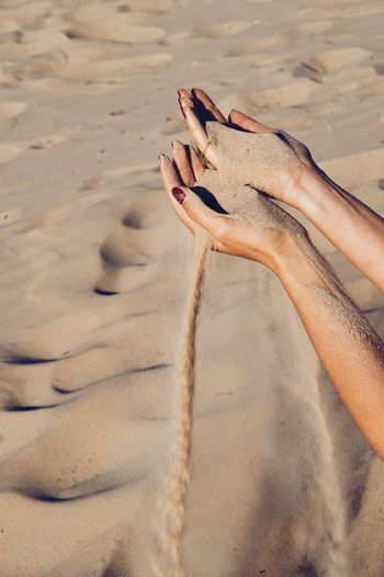 Cropped hands holding sand