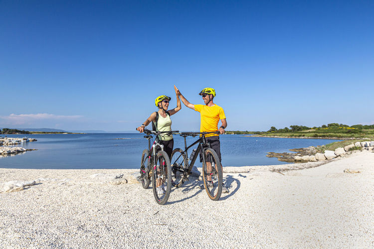 People riding bicycle on beach against clear sky