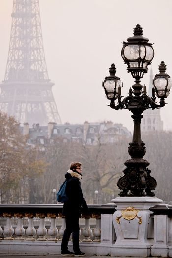 Full length of woman standing on bridge against eiffel tower in city
