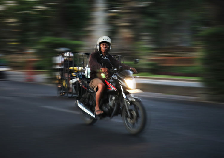Portrait of man riding motorcycle on road