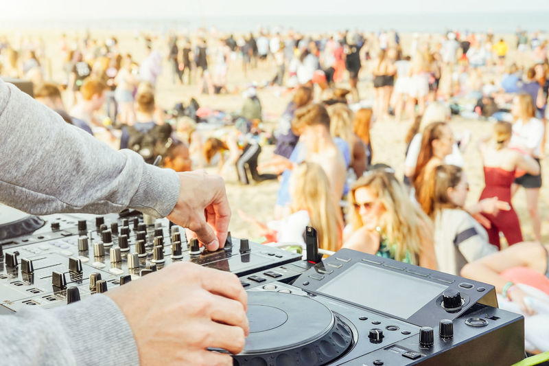 Close up of DJ's hand playing music at turntable at beach party festival - Crowd people dancing and having fun in club outdoor - Concept of youth summer party lifestyle Analog Audio Band Beach Buttons California Cd Celebration Club Concert Crowd Dance Deck Deejay Disc Disco Dj Edm Entertainment Event Fest Festival Fun Future Hand Hip Hop Holiday House Ibiza Instruments Lifestyle Light Man Miami Mixer Mixing Music Party People Player Playing Set Show Sound Stage Summer Sunset Technology Travel Turntable