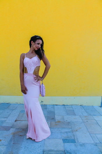 Full length of fashionable young woman standing against yellow wall