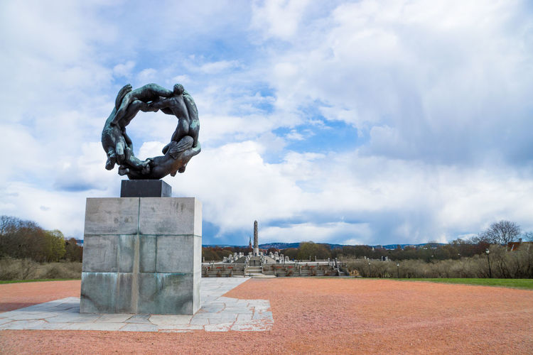 Low angle view of sculpture at gustav vigeland sculpture park against cloudy sky