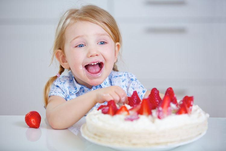 Cute smiling girl eating cake at home