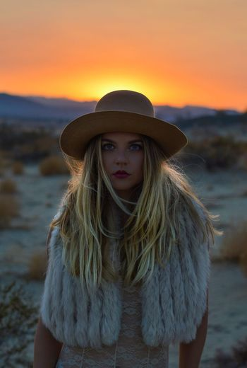 Portrait of beautiful woman standing against orange sunset sky