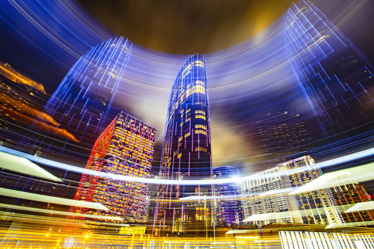 Digital composite image of illuminated modern buildings in city at night