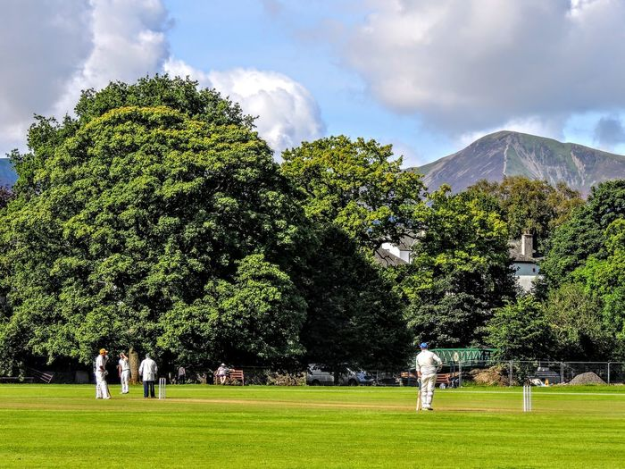 Tree Plant Group Of People Sky Nature Cloud - Sky Mountain Men Day Green Color Grass Land People Adult Outdoors Sport Architecture Leisure Activity Group Environment Cricket Match Cricket Field