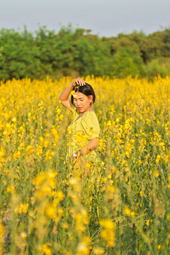 Woman standing by yellow flowers on field