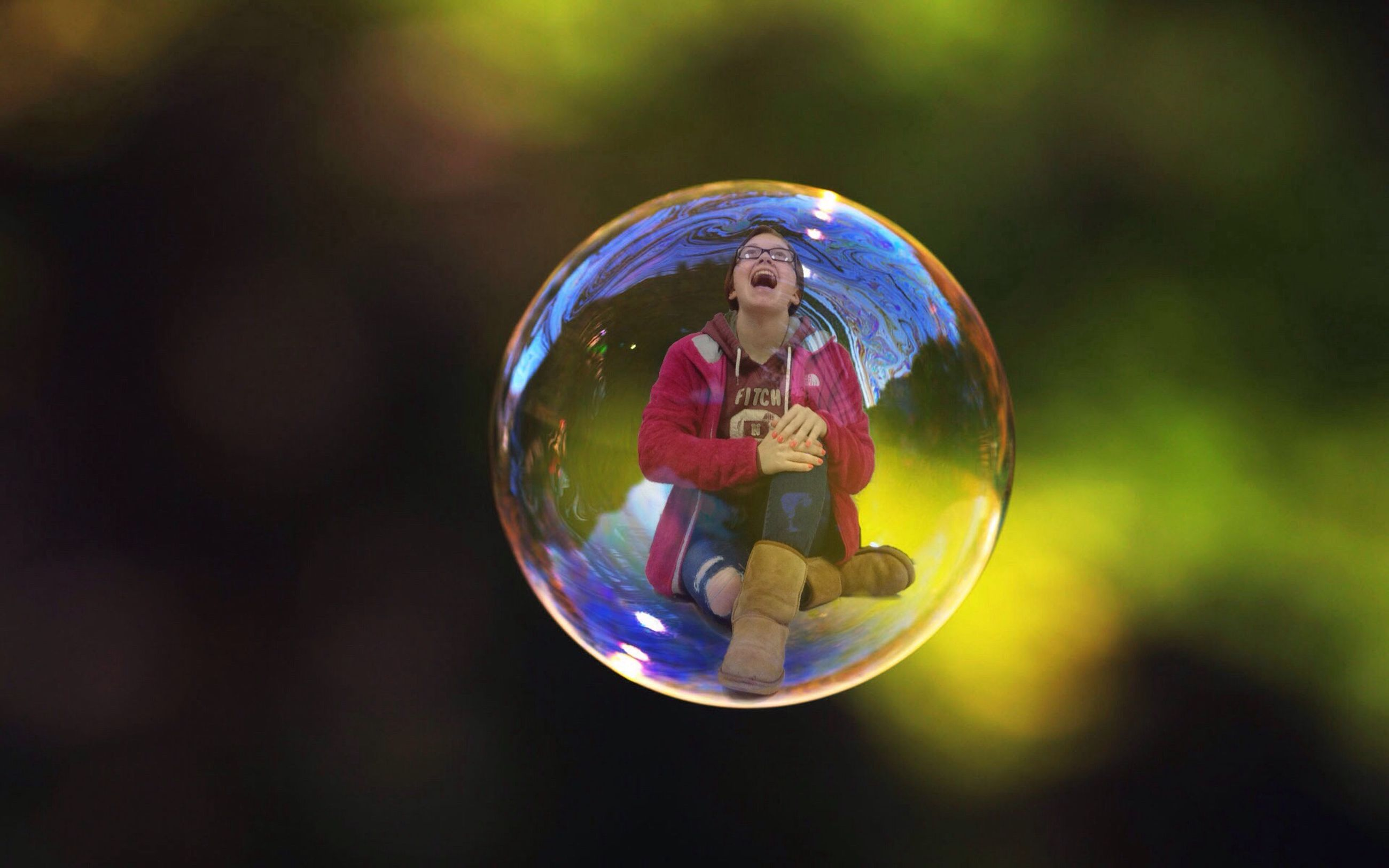 focus on foreground, bubble, close-up, childhood, sphere, reflection, selective focus, transparent, ball, multi colored, glass - material, circle, leisure activity, blue, mid-air, day, fragility, outdoors