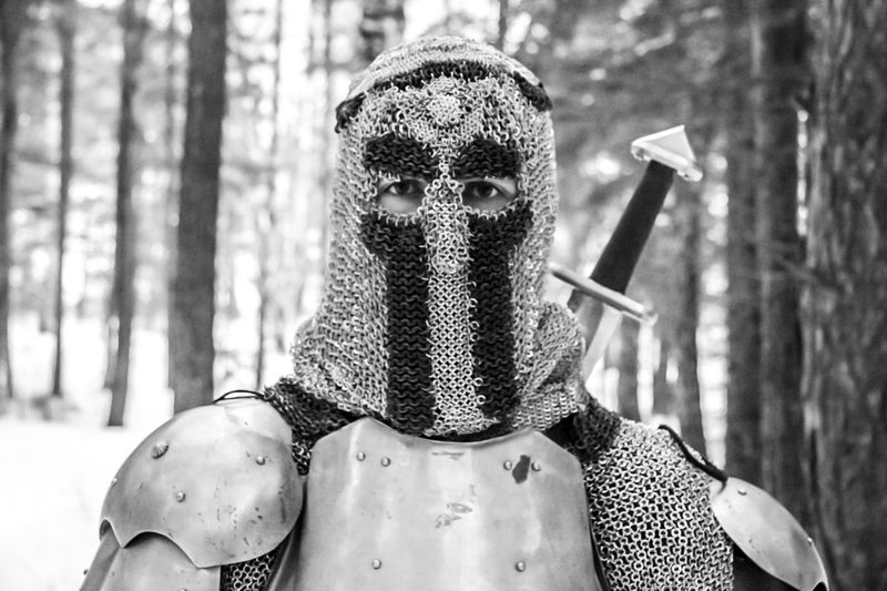 Portrait of man in warrior suit against trees in forest