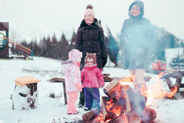 Family spending time together outdoors in the winter. Parents with children gathered around the campfire preparing marshmallows and snacks to toasting over the campfire using wooden sticks Winter Child Outdoors Childhood Boy Girl Cold Enjoyment Enjoy Kid Children Wintery Winter Snow Snowing Picnic Family Eating Campfire Roasting Marshmallows Snack Roasted Spending Time