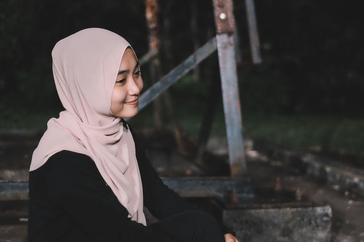 Smiling woman wearing hijab looking away at park