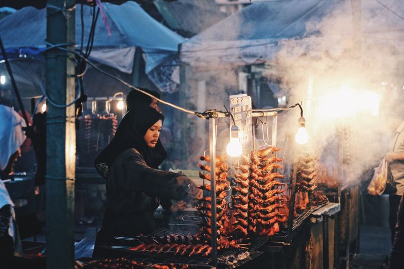 Woman preparing food in market stall at night