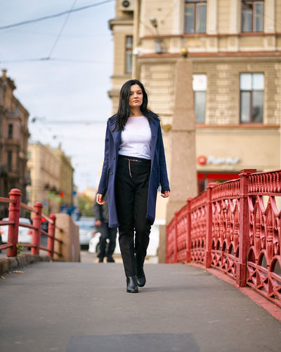 Full length portrait of young woman walking in city