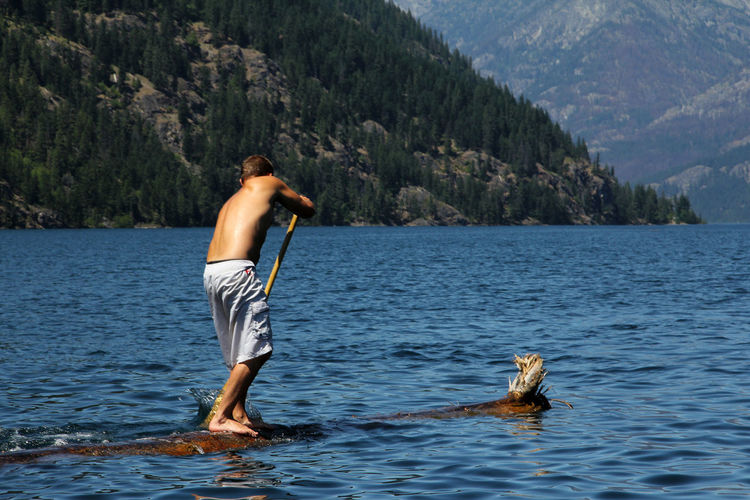 Full Length Of Shirtless Man Paddleboarding In Sea Against Tree Mountains