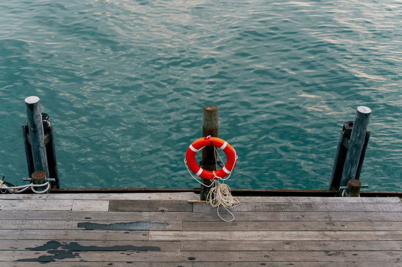 high angle view of a Lifebelt hanging on a wooden post at the railing Water Day Nature Outdoors High Angle View Safety Wood - Material Pier Rope Lifebelt Security Turquoise Colored Sea Ocean Pier Tourism Marine Railing Nautical Vessel No People Lifestyles Leisure Activity Calm Cruise