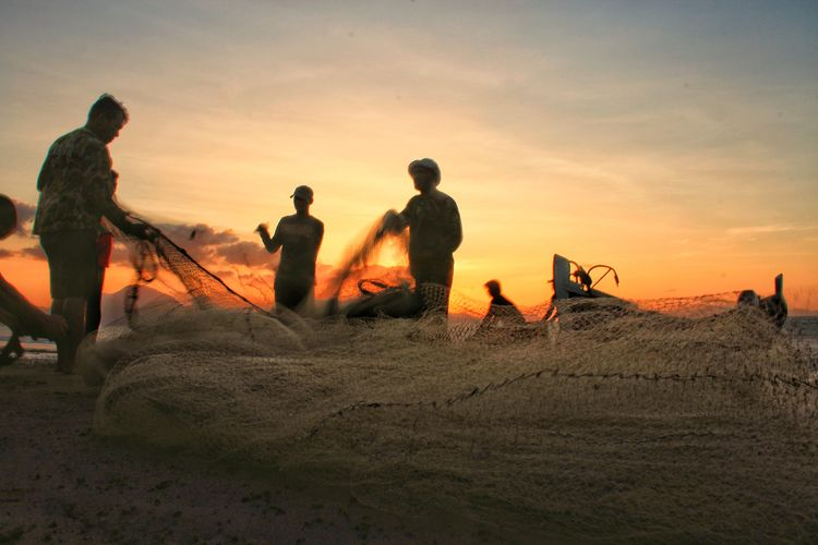 Army soldiers holding fishing net at beach against sky during sunset