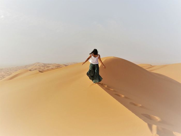 Rear view of young woman walking on sand dune at desert