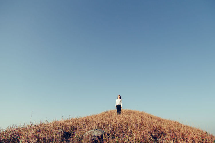 Low Angle View Of Woman Standing On Hill Against Clear Sky