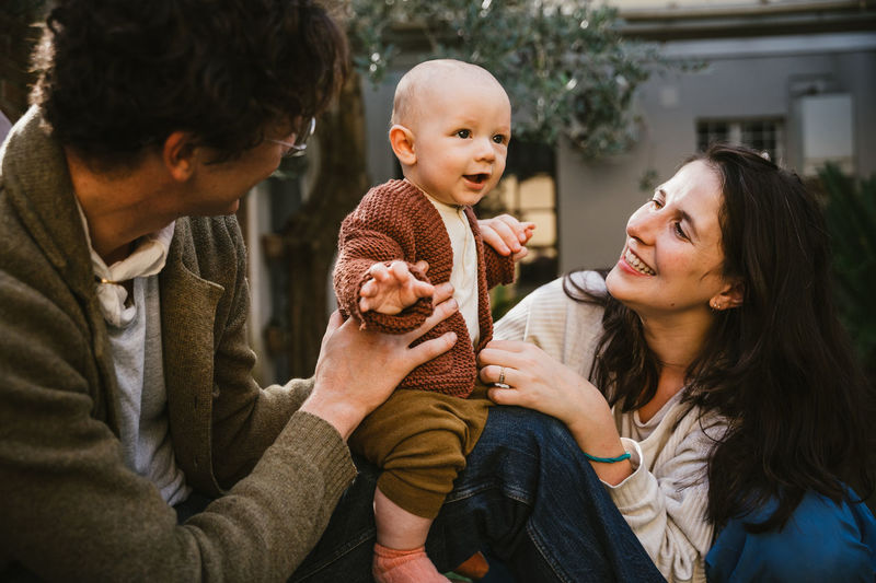 Cheerful father and mother holding son outdoors