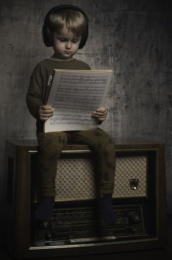 Full Length Of Cute Boy Reading Musical Note While Sitting On Radio At Home