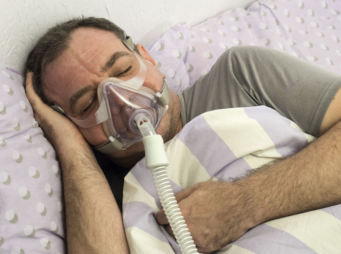 Close-up of man wearing oxygen mask while sleeping on bed at home