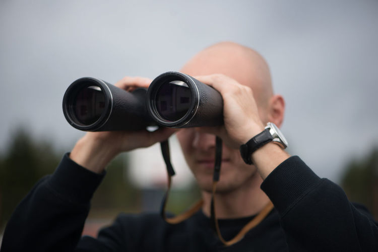 Close-Up Of Mid Adult Man Looking Through Binoculars While Standing Against Sky