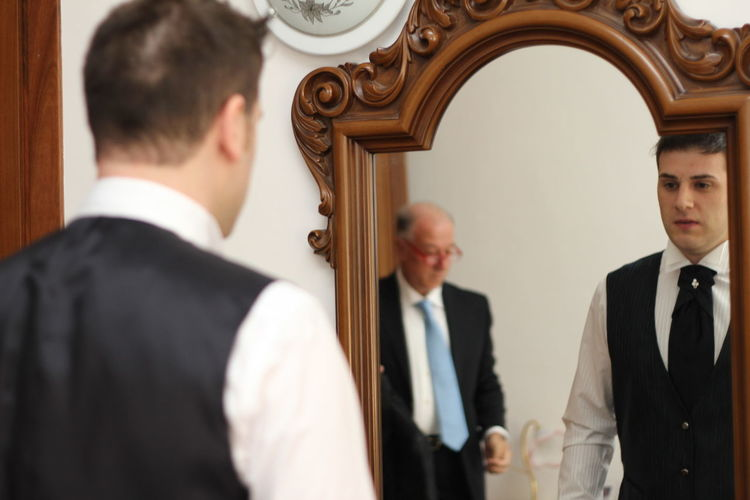 Rear view of groom reflecting in mirror at home