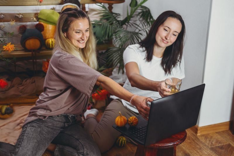 Smiling women holding drinks while video calling on laptop at home