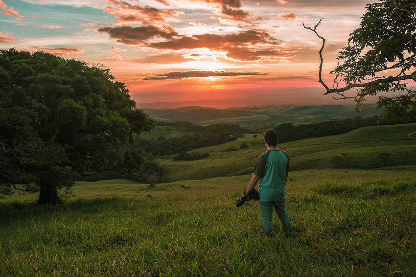 Captando atardeceres en la provincia de Guanacaste Beauty In Nature Day Full Length Grass Landscape Lifestyles Nature One Person Outdoors Real People Sky Sunset Tranquil Scene Tree Walking Summer Exploratorium