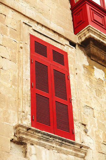 Low angle view of red window on wall of building
