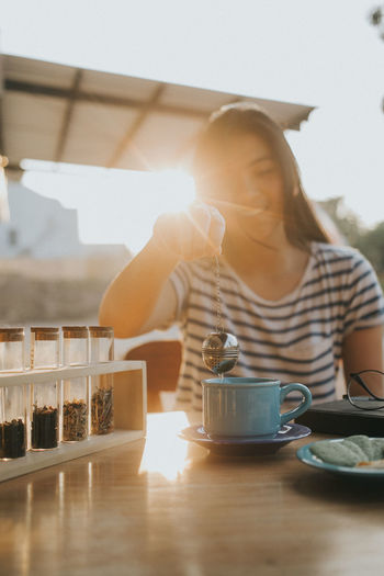 Young woman having tea at cafe during sunset