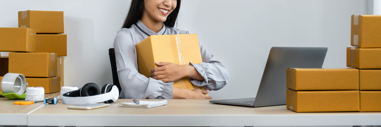 Young woman holding box while sitting at office