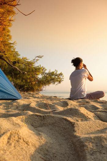 Performing pranayama against the sunrise. Breathing Camping Meditation Yoga Yoga Pose Dusky Leisure Activity Lifestyles Pranayama Sand Sunrise Vacations Yoga Breathing Yogic Breath