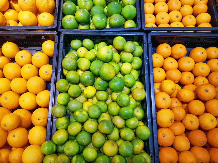 Full frame vibrant background of piles of fresh orange fruits in trays