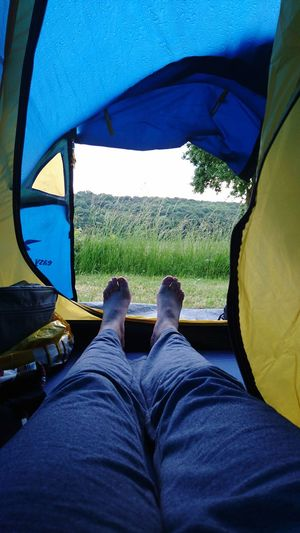 Low section of man relaxing at tent