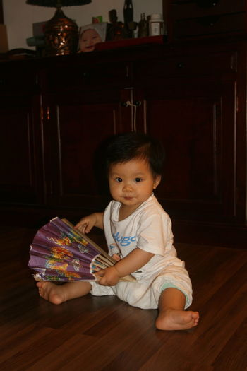 Portrait of cute baby with hand fan sitting on floor at home
