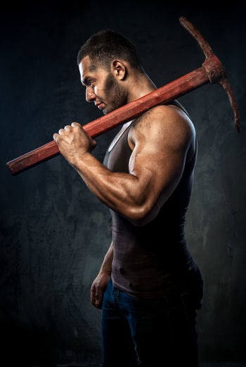 Side View Of Muscular Man Holding Pick Axe Against Wall