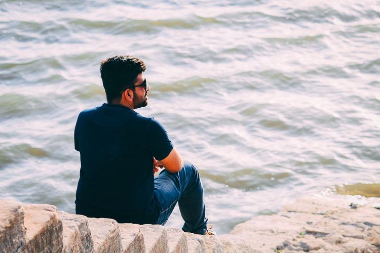 Man sitting on rock looking at sea
