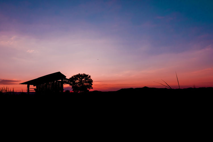 Silhouette houses against sky during sunset