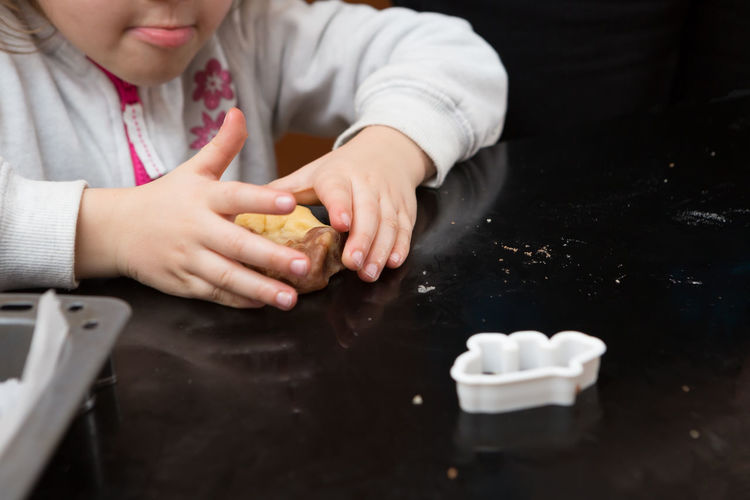 Midsection of girl preparing cookie on kitchen island at home