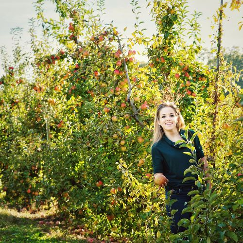 Portrait Of Smiling Young Woman Standing By Apple Trees